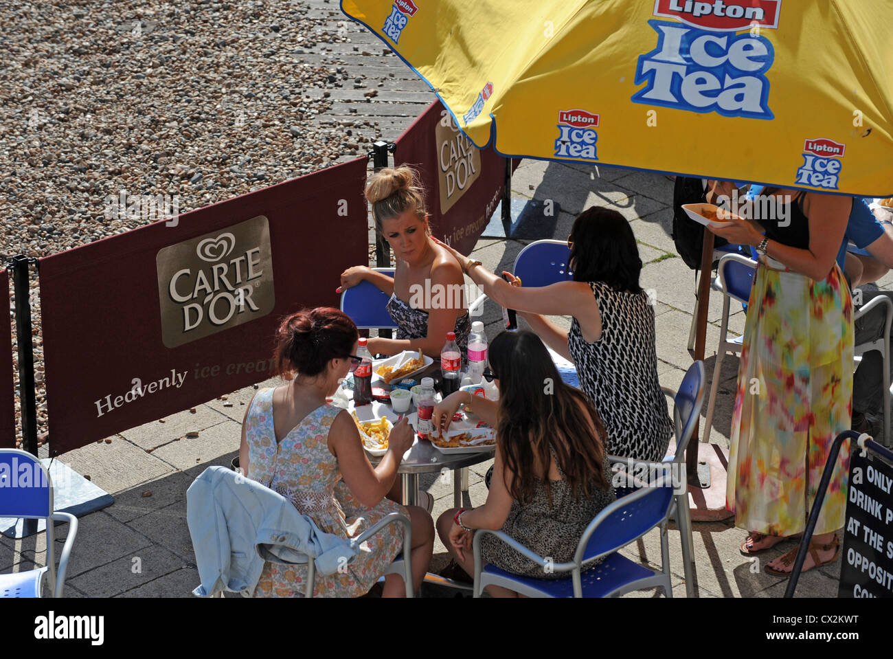 Young woman applying suncream to a friends back Brighton UK 2012 - Stock Image