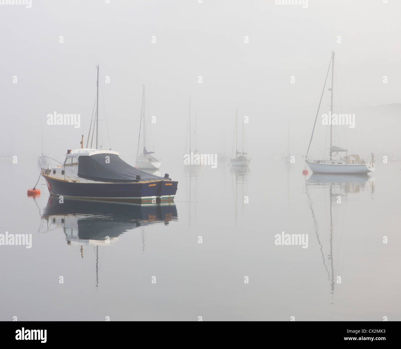 Boats in the mist on Kingsbridge Estuary, Salcombe, South Hams, Devon, England. Autumn (September) 2010. - Stock Image