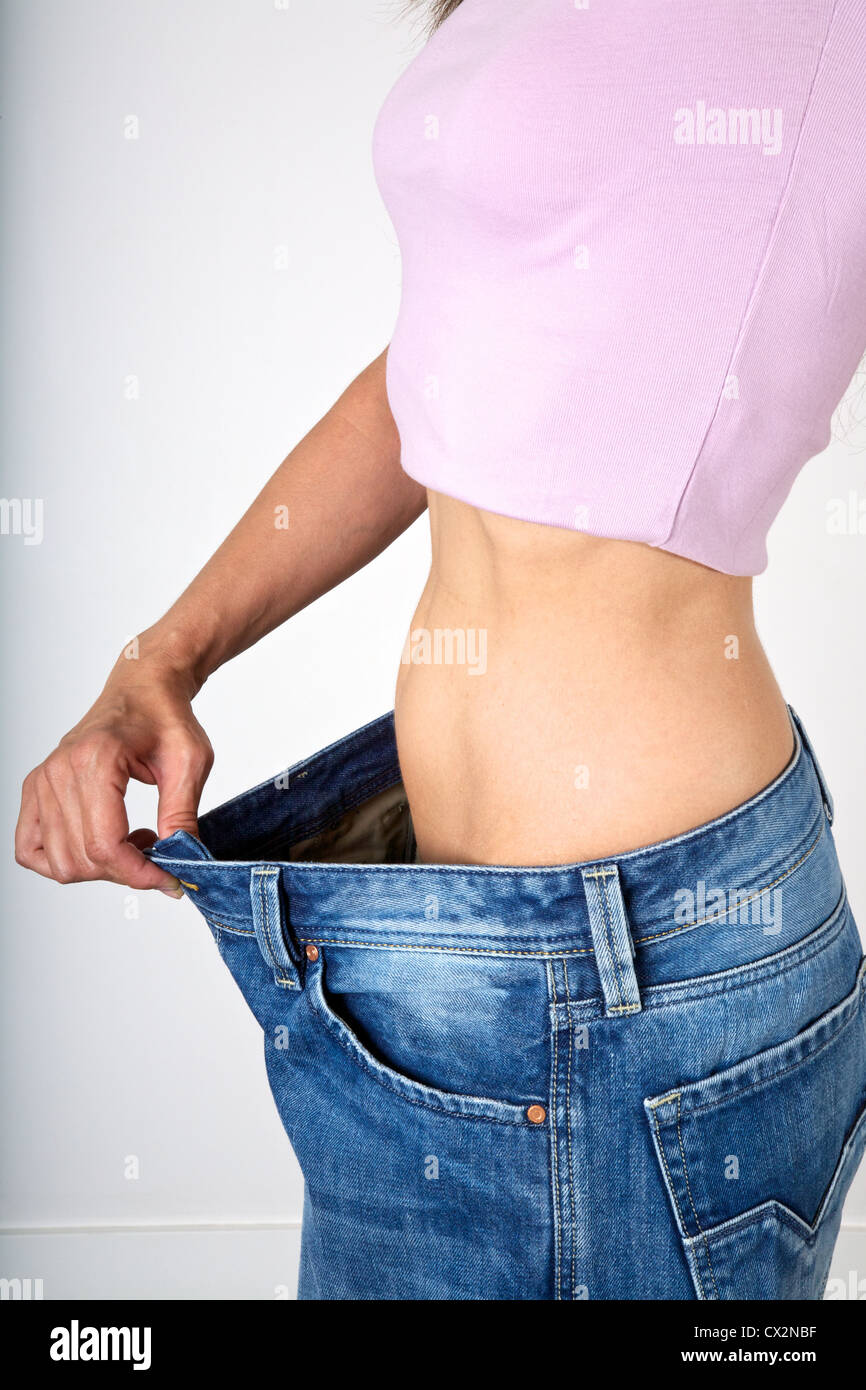 slim female hand showing her jeans are very big - Stock Image