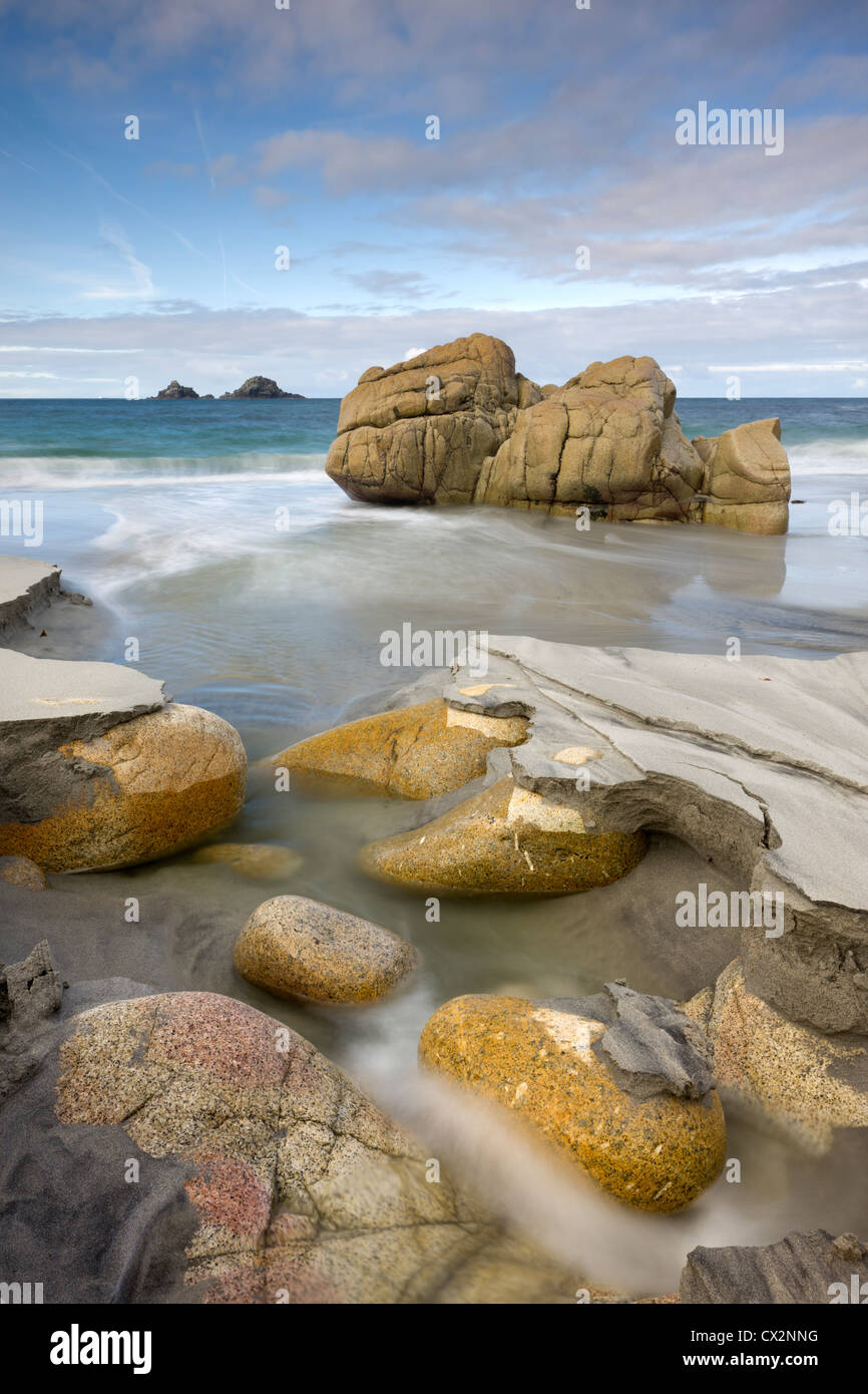 Smooth granite boulders on the sandy beach at Porth Nanven, Cornwall, England. Autumn (October) 2010. - Stock Image