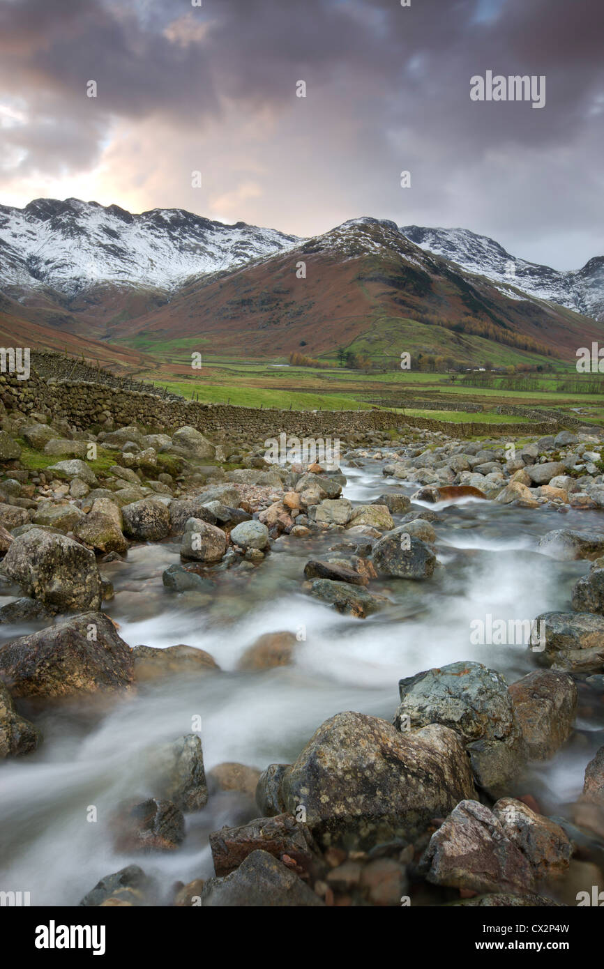 Redacre Gill river tumbling over rocks towards the snow capped mountains surrounding Great Langdale - Stock Image