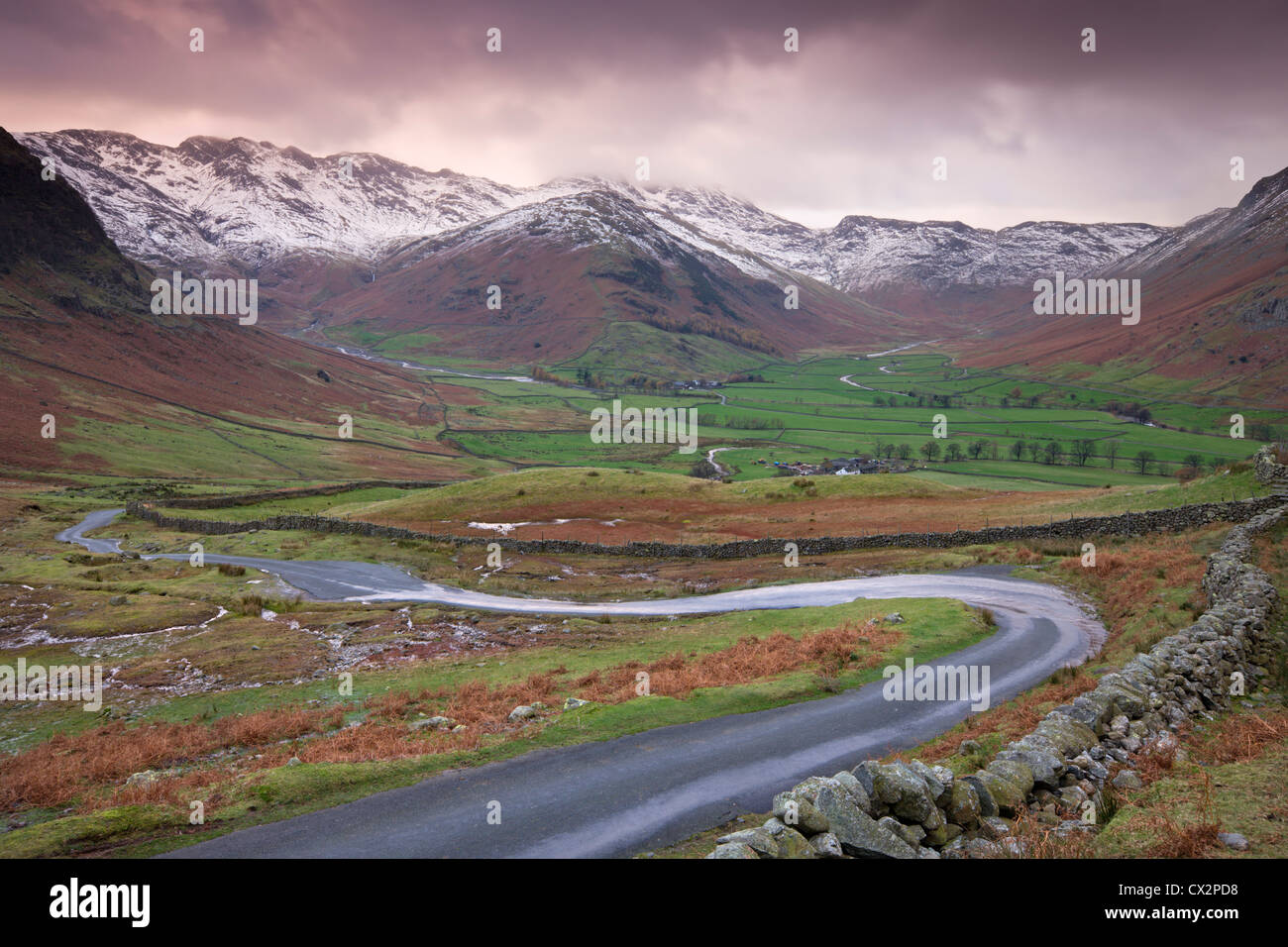 Small winding road leading into the Langdale Valley, surrounded by snow clad mountains, Lake District - Stock Image