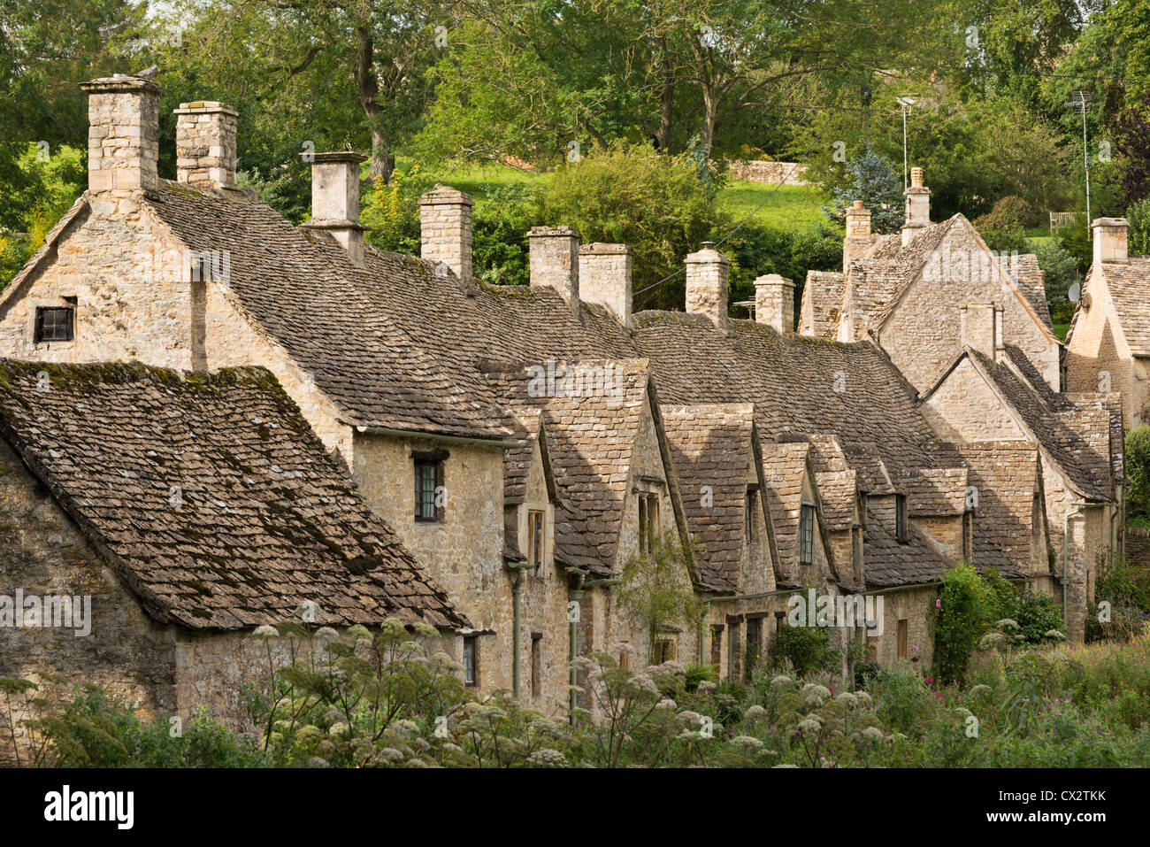 Picturesque cottages at Arlington Row in the Cotswolds village of Bibury, Gloucestershire, England. Summer (September) - Stock Image