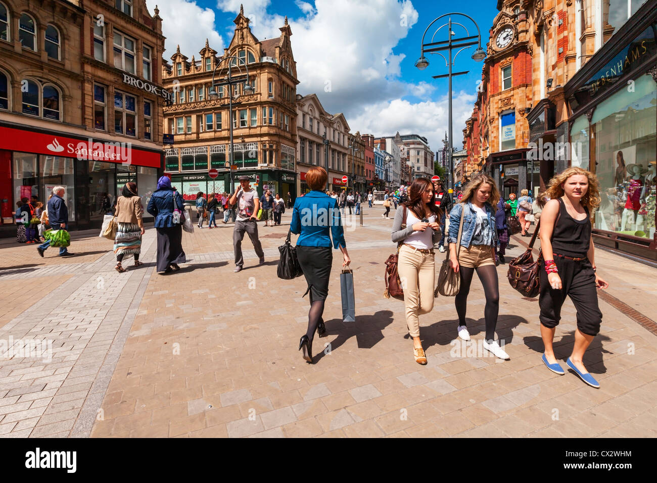 Shoppers and lunch time crowds in Briggate, the main shopping street in the city of Leeds, West Yorkshire, England. - Stock Image