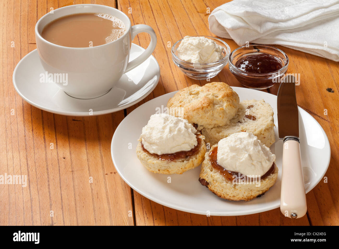 Devon cream tea, scones, jam, cream and a cup of tea, on an old pine table. - Stock Image