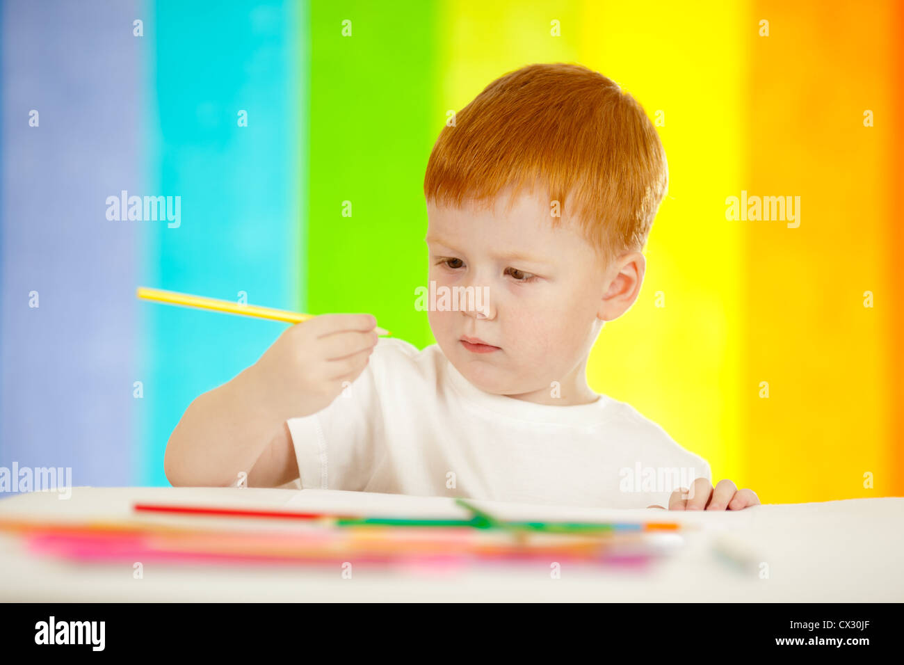 Redheaded adorable boy drawing with yellow pencil on rainbow background Stock Photo