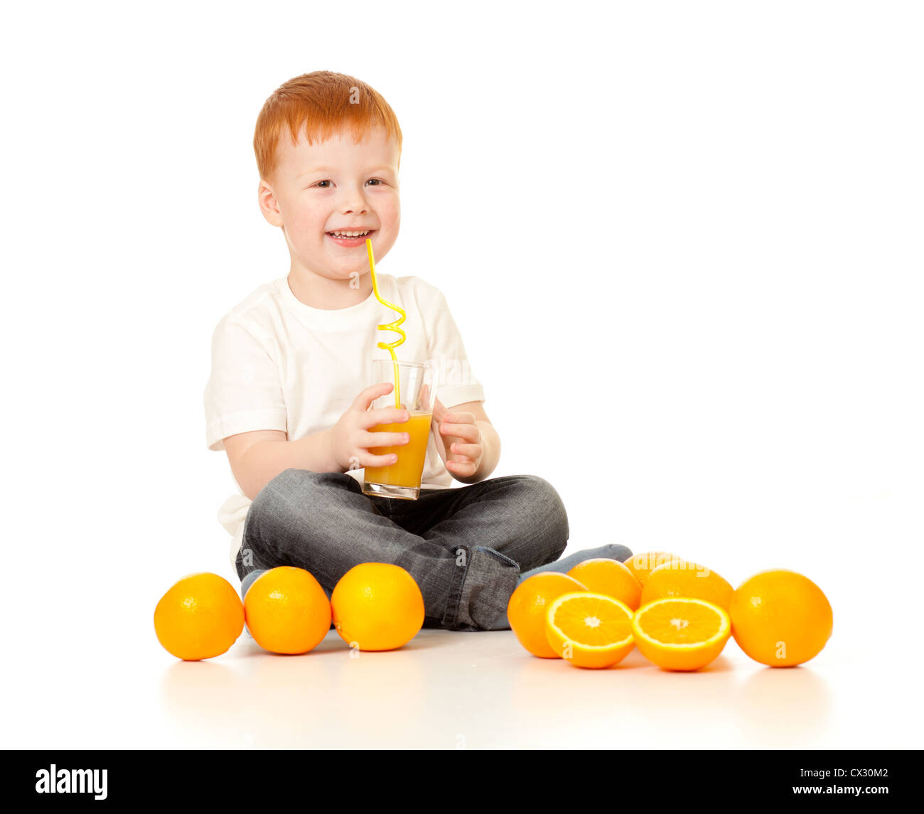red-haired boy with ornage juice and oranges isolated on white - Stock Image