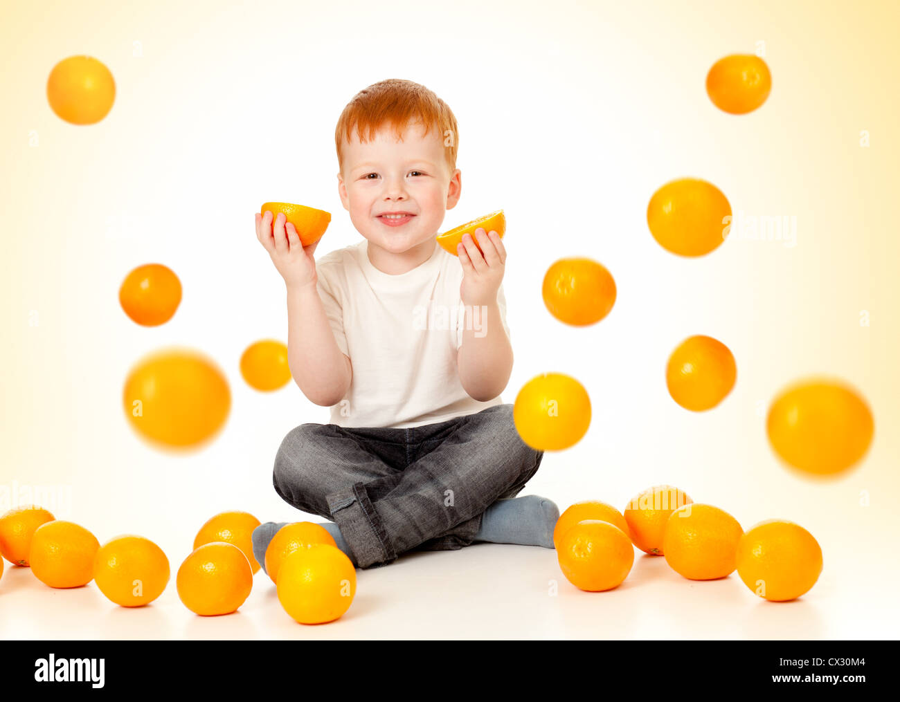 redheaded boy with falling oranges - Stock Image