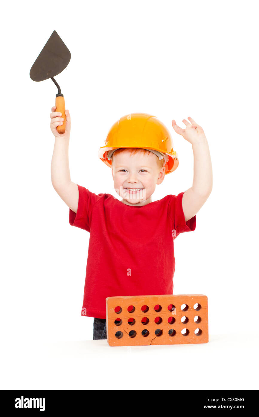 Boy in hard hat with trowel and brick isolated - Stock Image