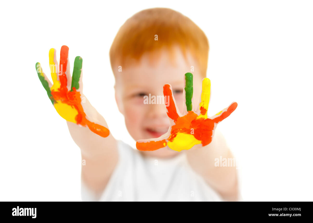 Adorable redheaded boy with focus on hands painted in bright colors Stock Photo