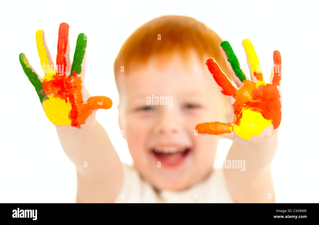 Adorable red-haired boy with focus on hands painted in bright colors Stock Photo