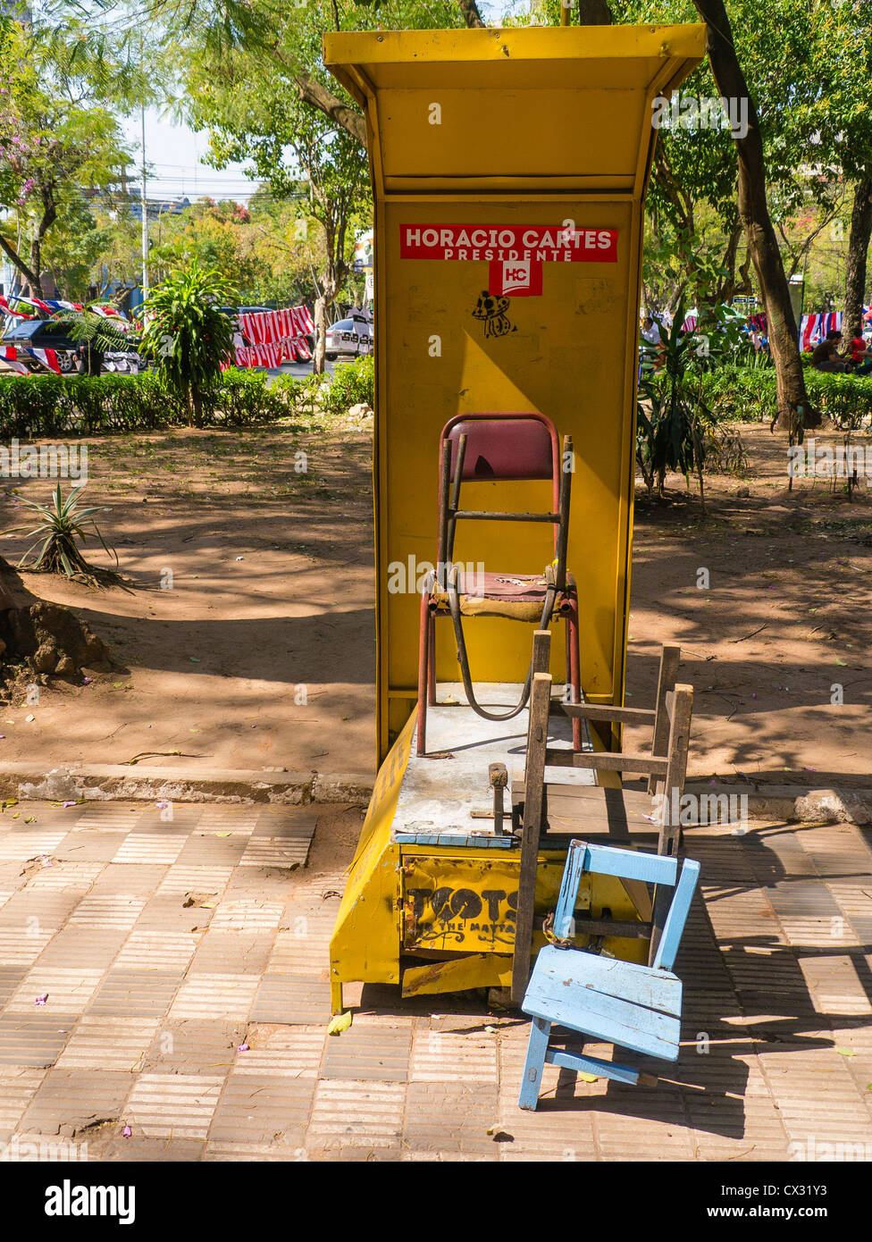 A shoe shine stand is unoccupied before business starts in a plaza in Asunción, Paraguay. - Stock Image
