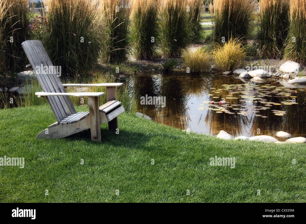 Astonishing A Wooden Lounge Chair Sitting On Grass Beside A Pool Filled Unemploymentrelief Wooden Chair Designs For Living Room Unemploymentrelieforg