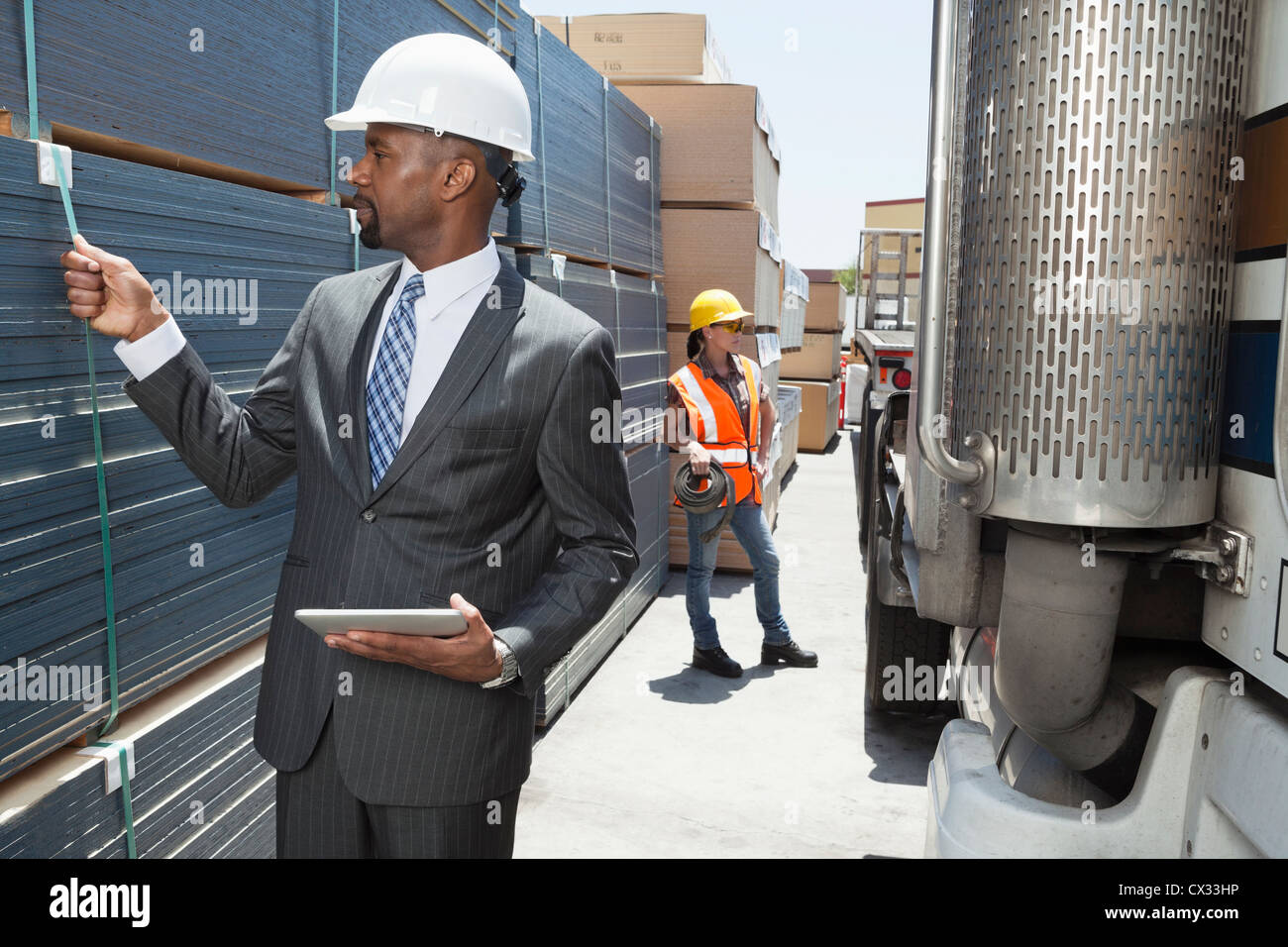 African American male engineer inspecting planks while female worker standing by flatbed truck - Stock Image