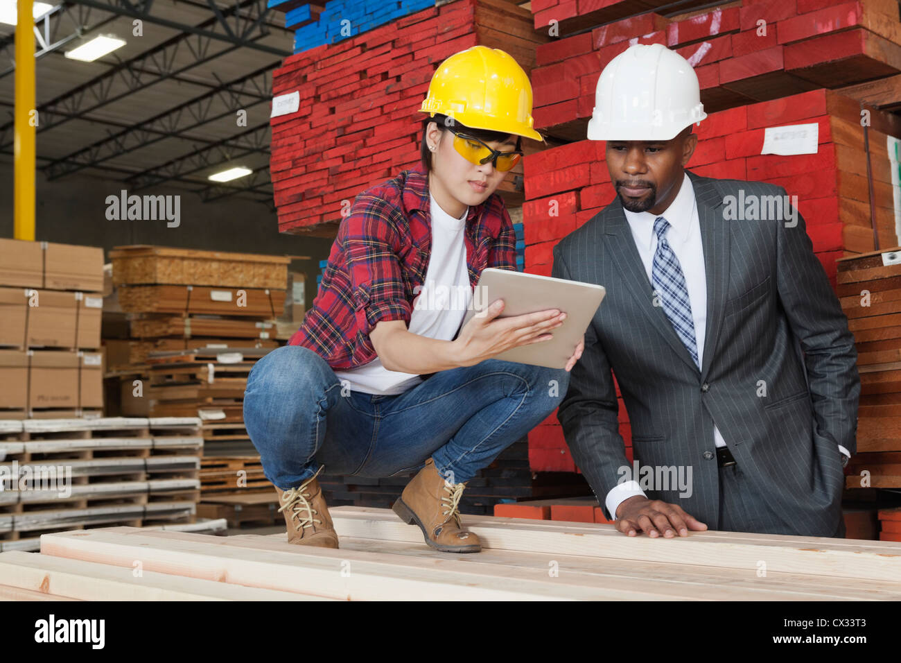 Female industrial worker showing something on tablet PC to male engineer - Stock Image