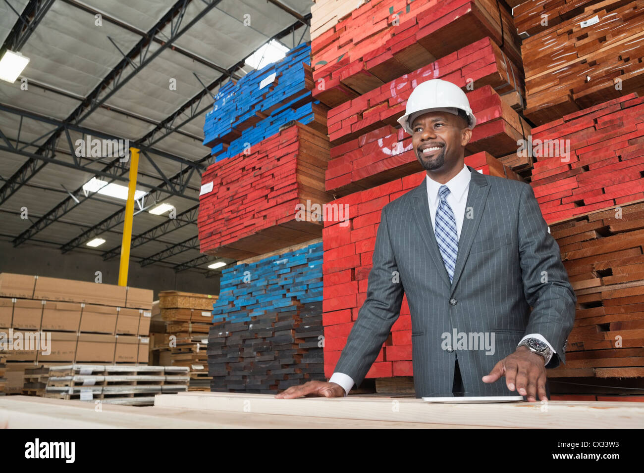 An African American male contractor standing in front of stacked wooden planks - Stock Image