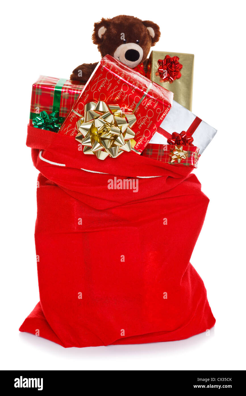 Red Christmas sack full of gift wrapped presents, isolated on a white background Stock Photo