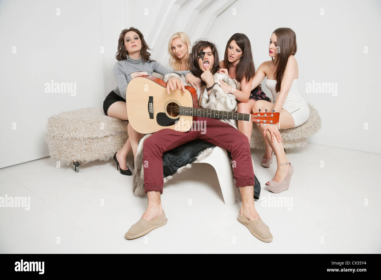 Portrait of young male guitarist sitting amid young female friends - Stock Image