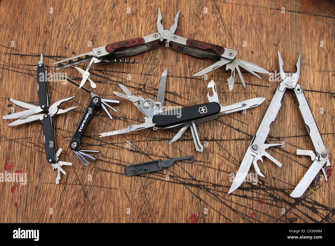 Penknives on a heavily worn table with their blades pulled out. - Stock Image