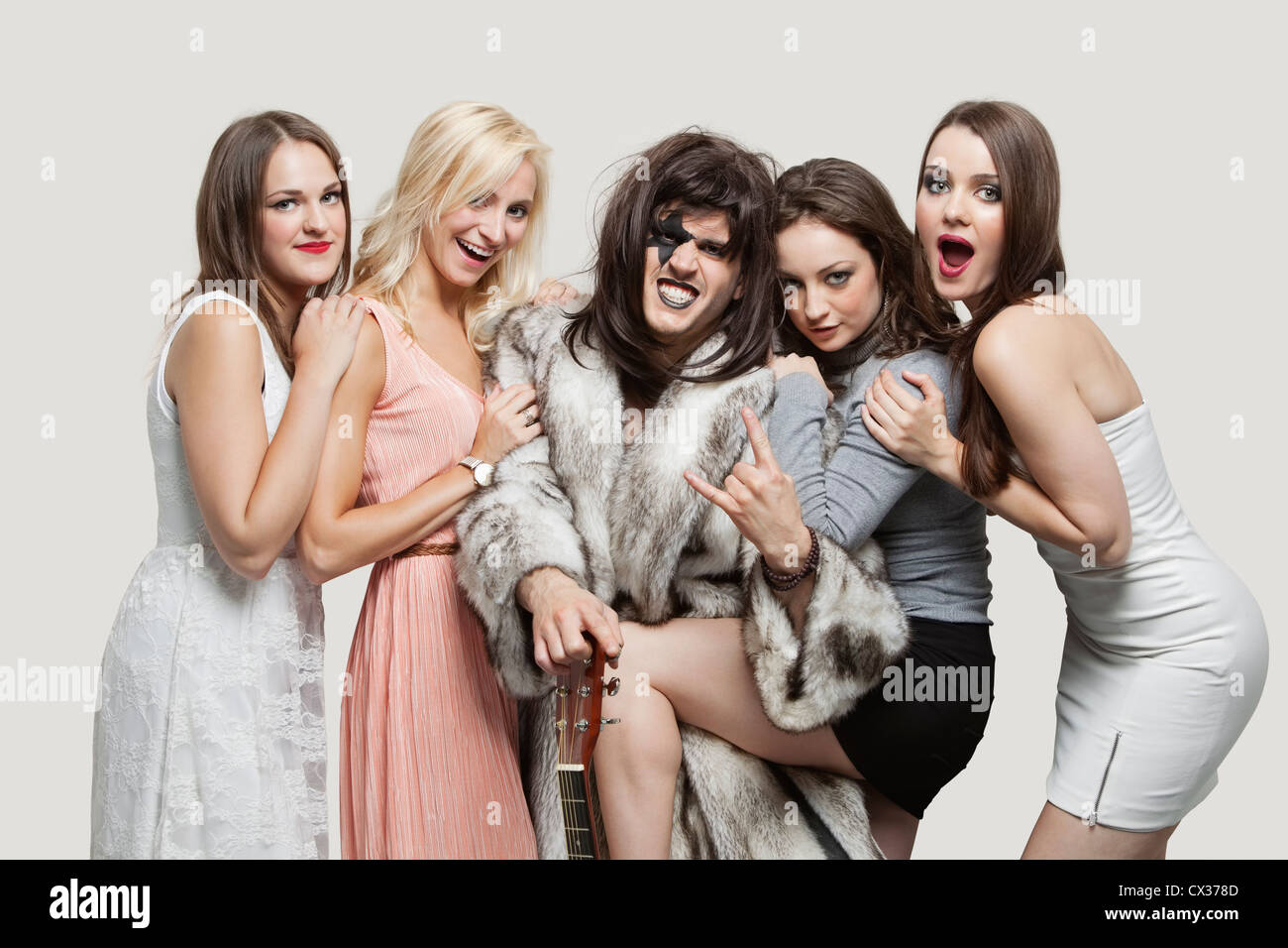 Young playboy with hand gesture amid happy women over gray background - Stock Image