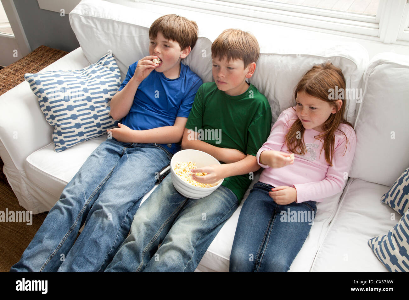 Three kids are sitting on the couch watching tv and eating popcorn. - Stock Image