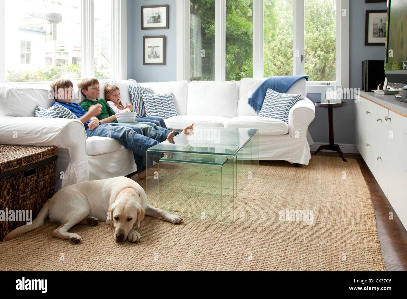 Three kids are on the couch watching tv. - Stock Image