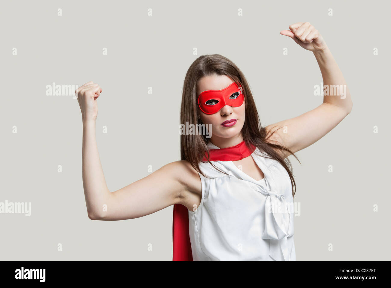 Portrait of a young woman in super hero costume flexing muscles over gray background  sc 1 st  Alamy & Portrait of a young woman in super hero costume flexing muscles over ...
