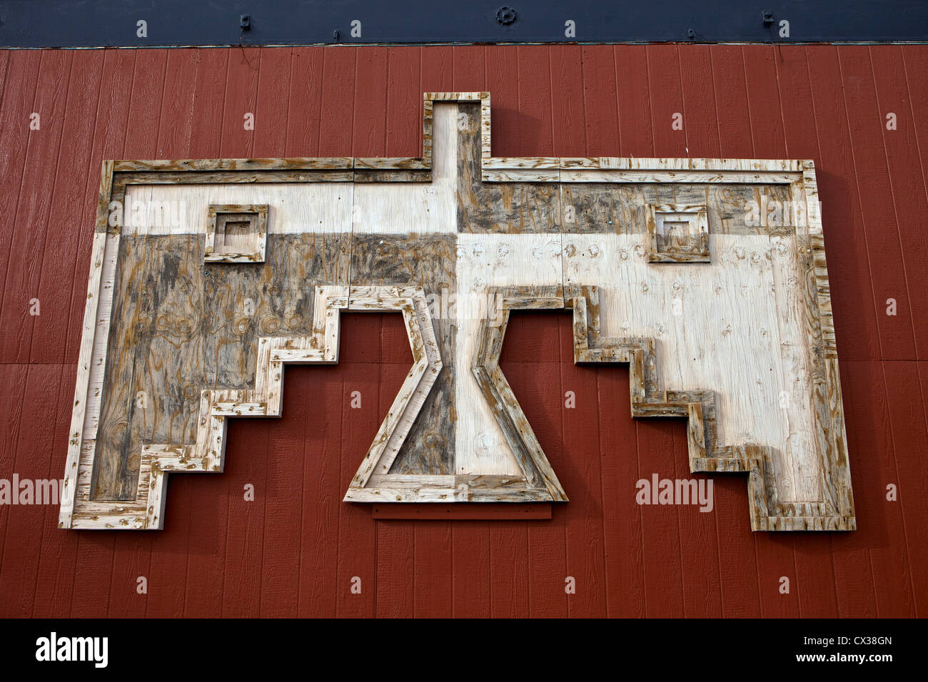 Fading wooden thunderbird on the side of a red building in Winslow, Arizona - Stock Image