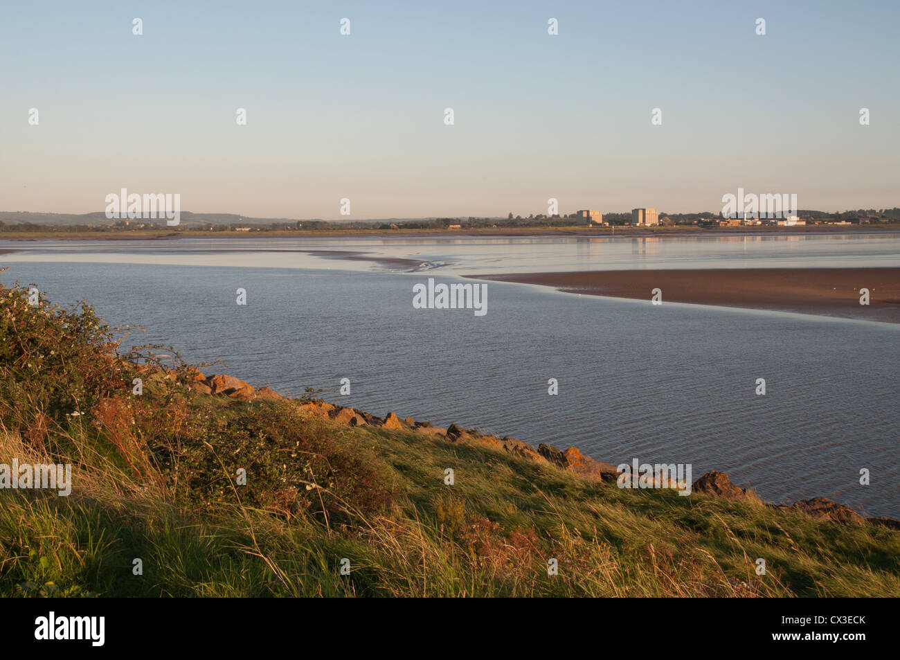 River Severn at low tide in low sunlight with grassy bank power station in background - Stock Image