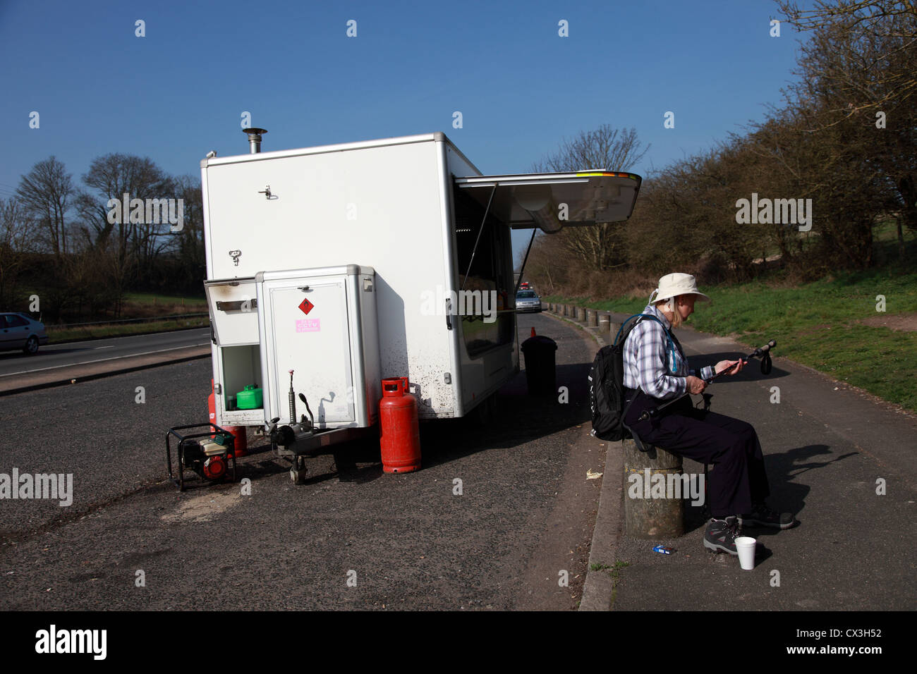 Lady walker having a cup of tea from a roadside cafe and preparing her sticks for a walk - Stock Image