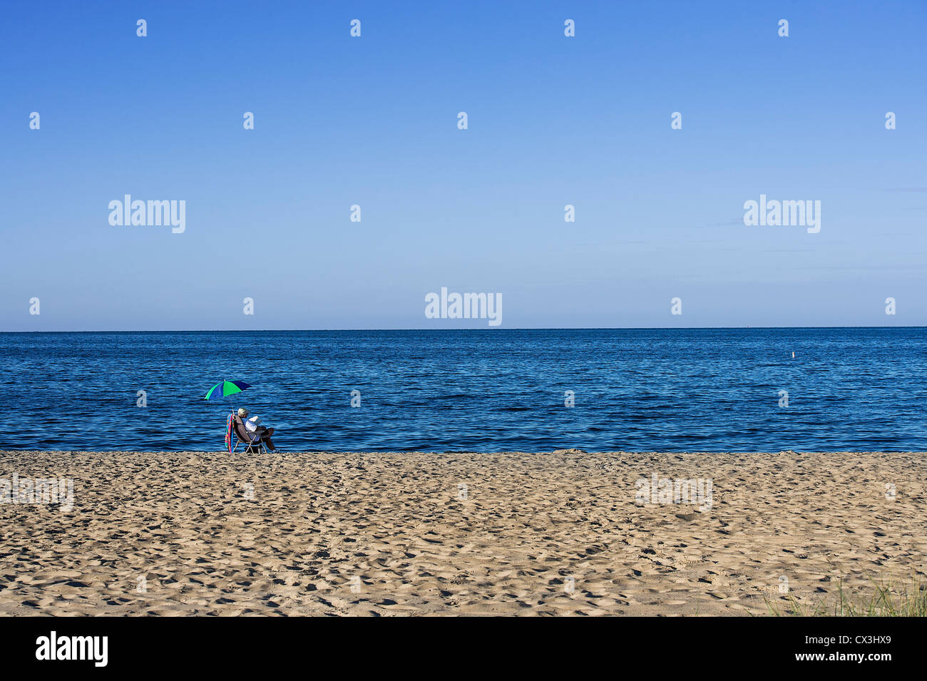 Retired man leisurely reading at the beach. - Stock Image