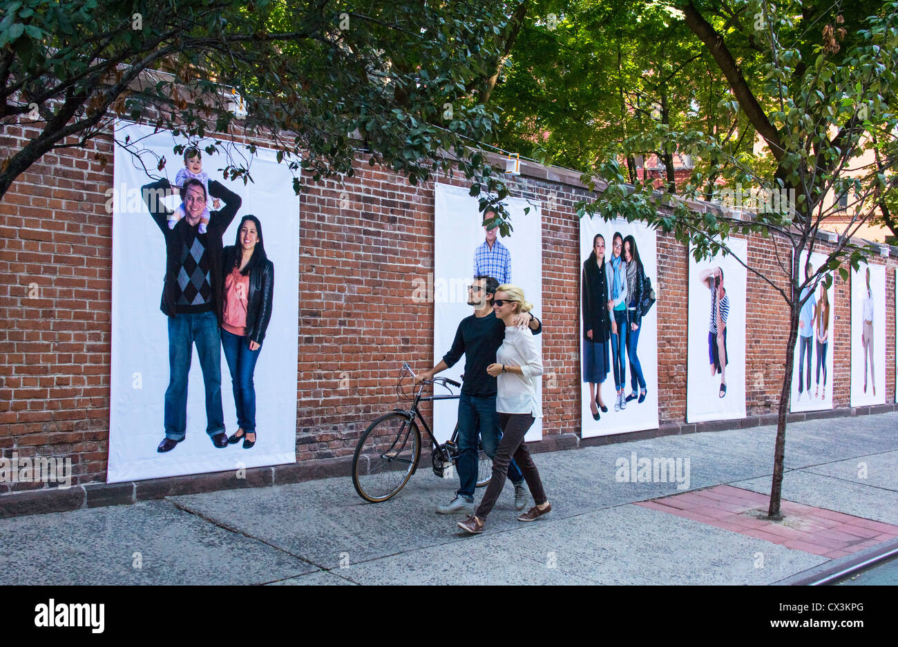 On Prince Street in the Nolita section of New York City, a couple with a bicycle view a wall of giant photo blowups - Stock Image