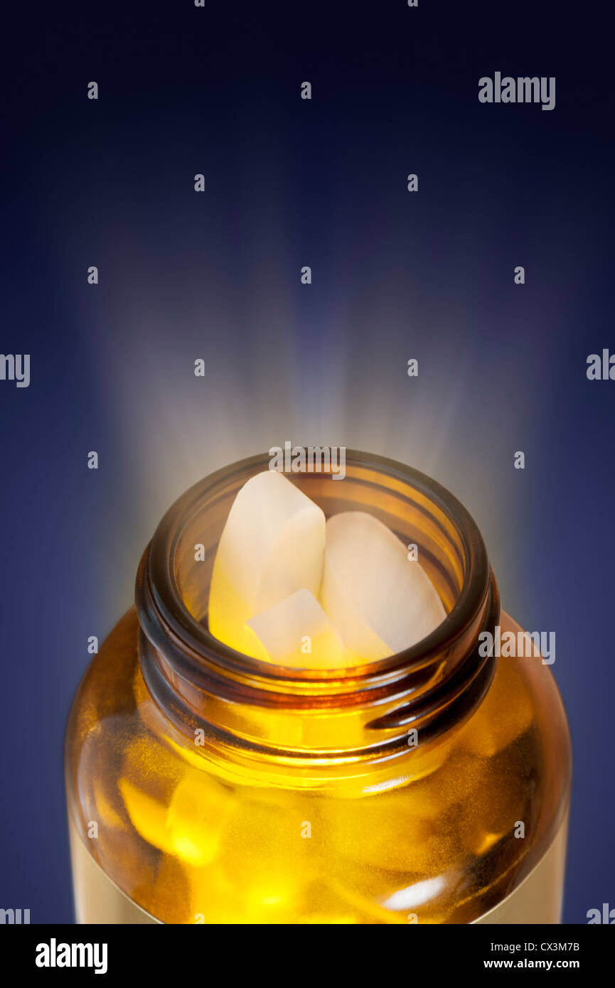 BOTTLE OF PILLS MIRACLE CURE CONCEPT with glow coming from within the bottle - Stock Image