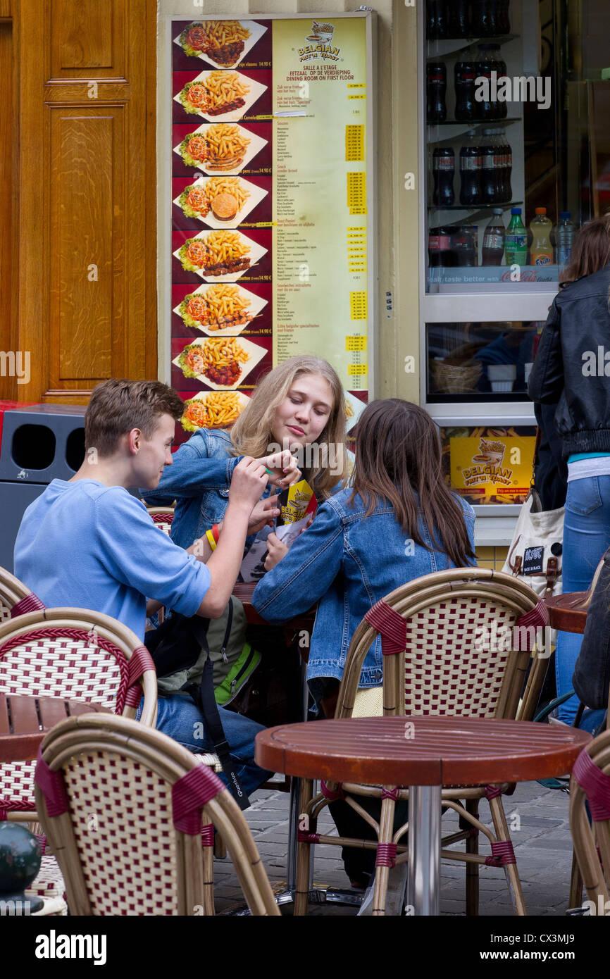 young teenagers boys girls eating fries outside - Stock Image