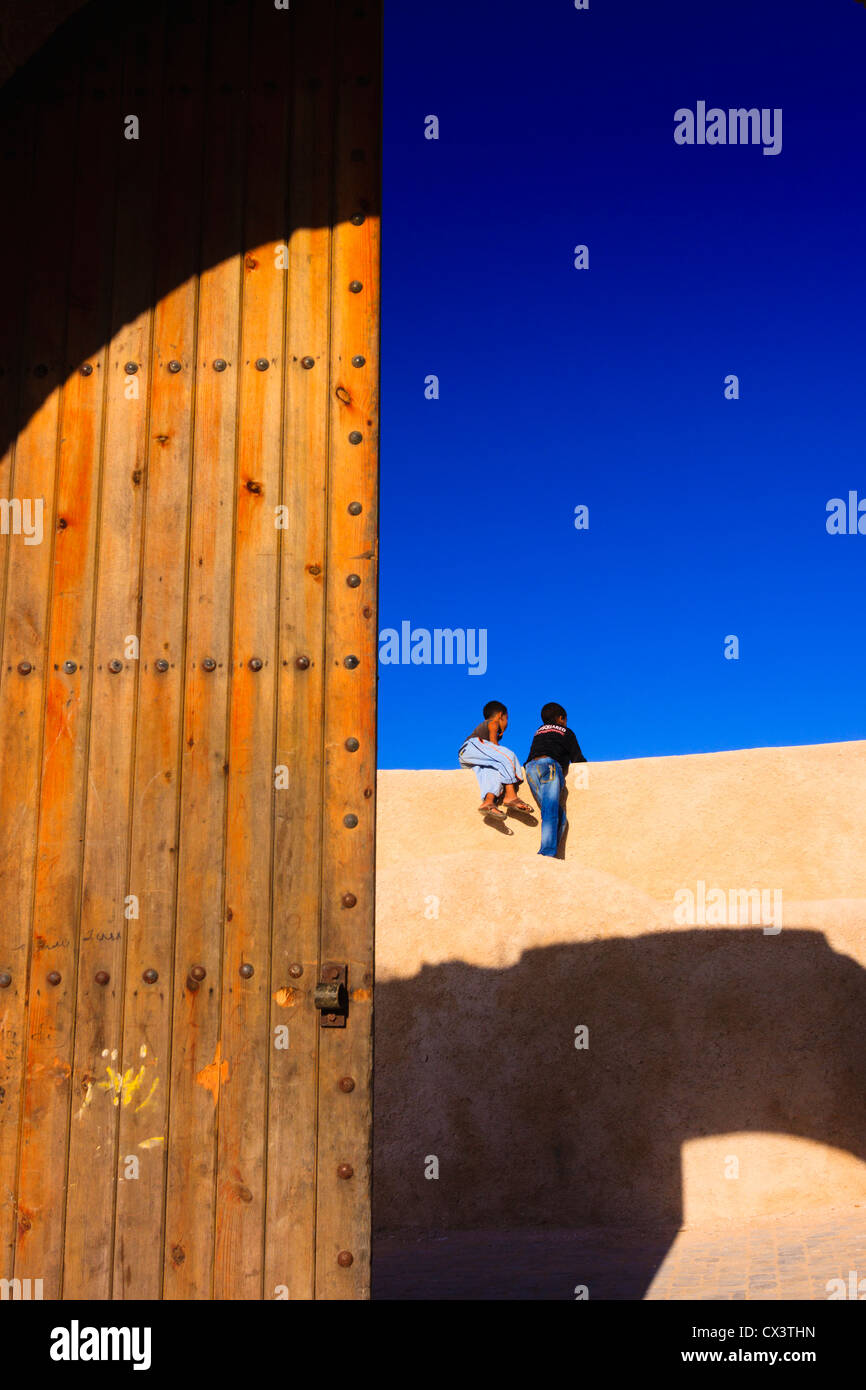 Two children at the Porte de la mer gate in the bastion walls of the Portuguese town in el Jadida, Atlantic Morocco - Stock Image