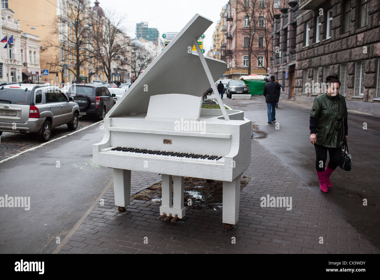 Pedestrians pass a white grand piano monument in downtown Kiev, Ukraine, Eastern Europe Stock Photo