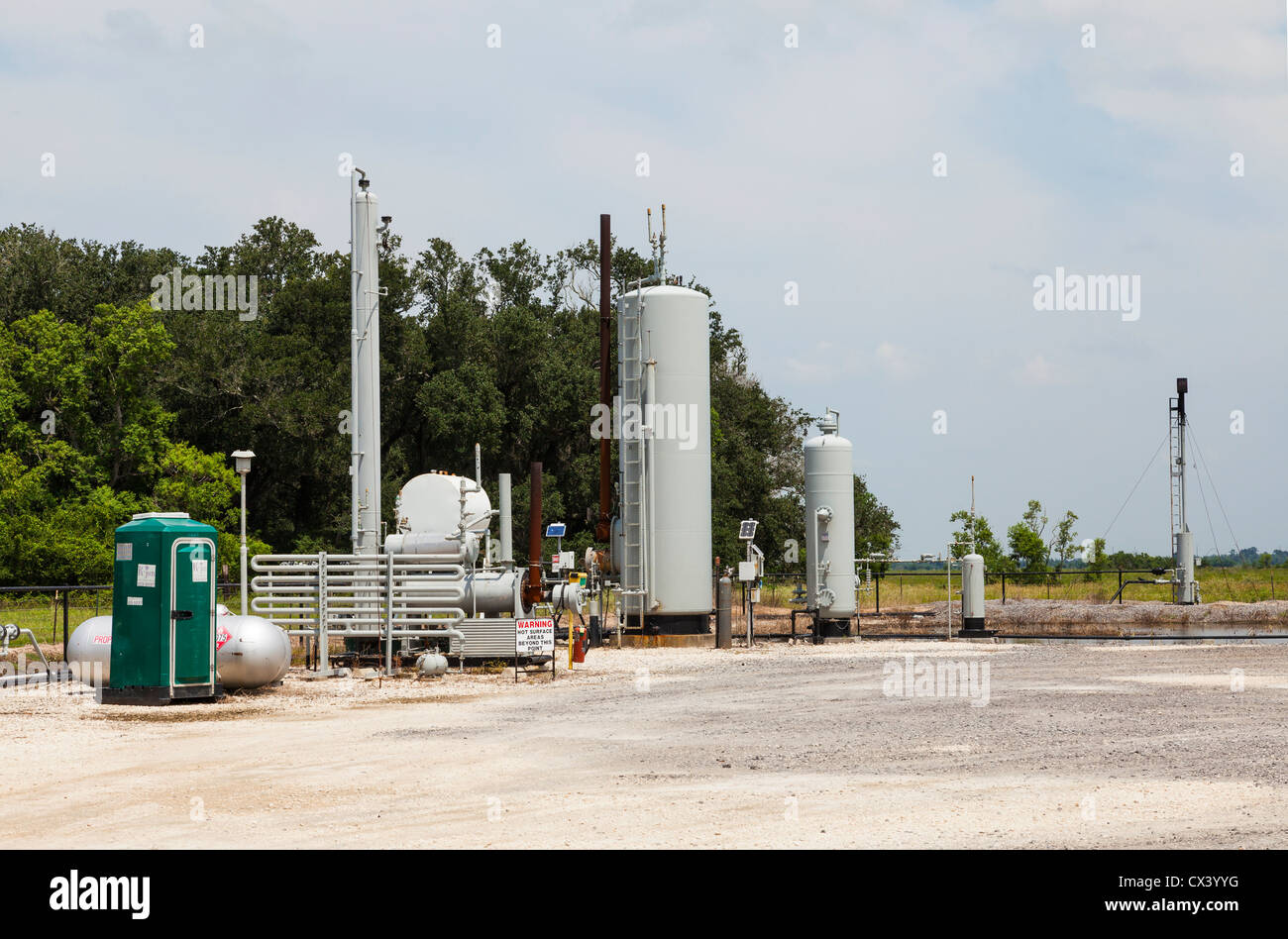 Remote crude oil pumping and truck loading facility for rural oil wells, showing flaring system. - Stock Image