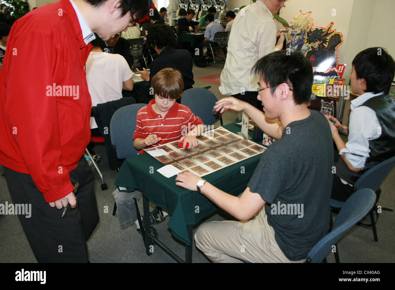 A referee is called to clarify rule of Yugioh card game between eight year old American boy and Japanese adult during - Stock Image