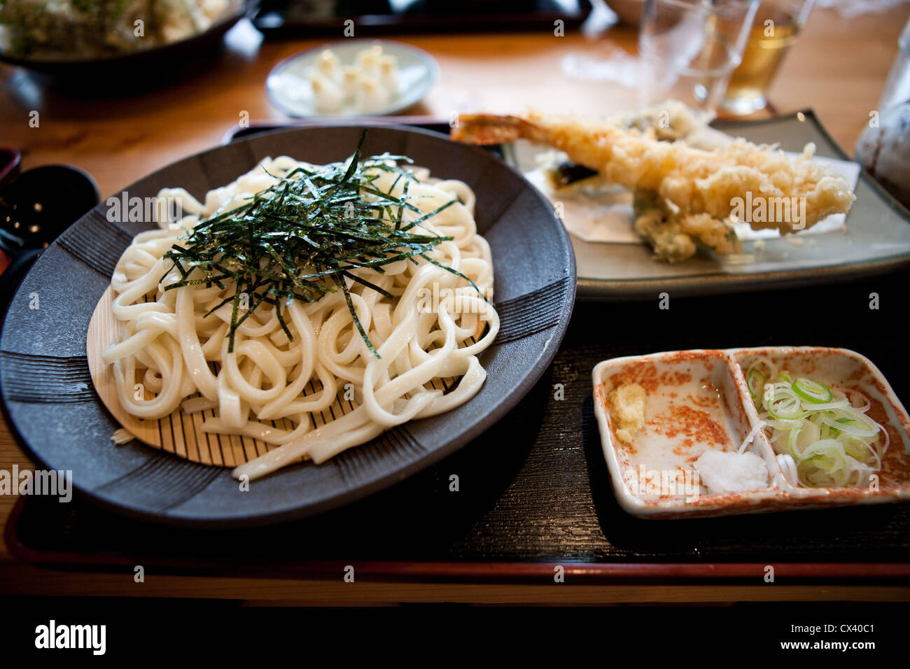 Traditional cold udon noodles served with shrimp tempura on the side. Stock Photo