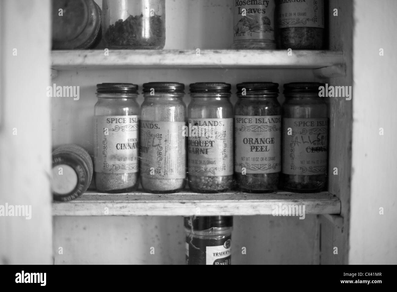 A house which has sat vacant for 20 years still has old spice jars in a cabinet. - Stock Image