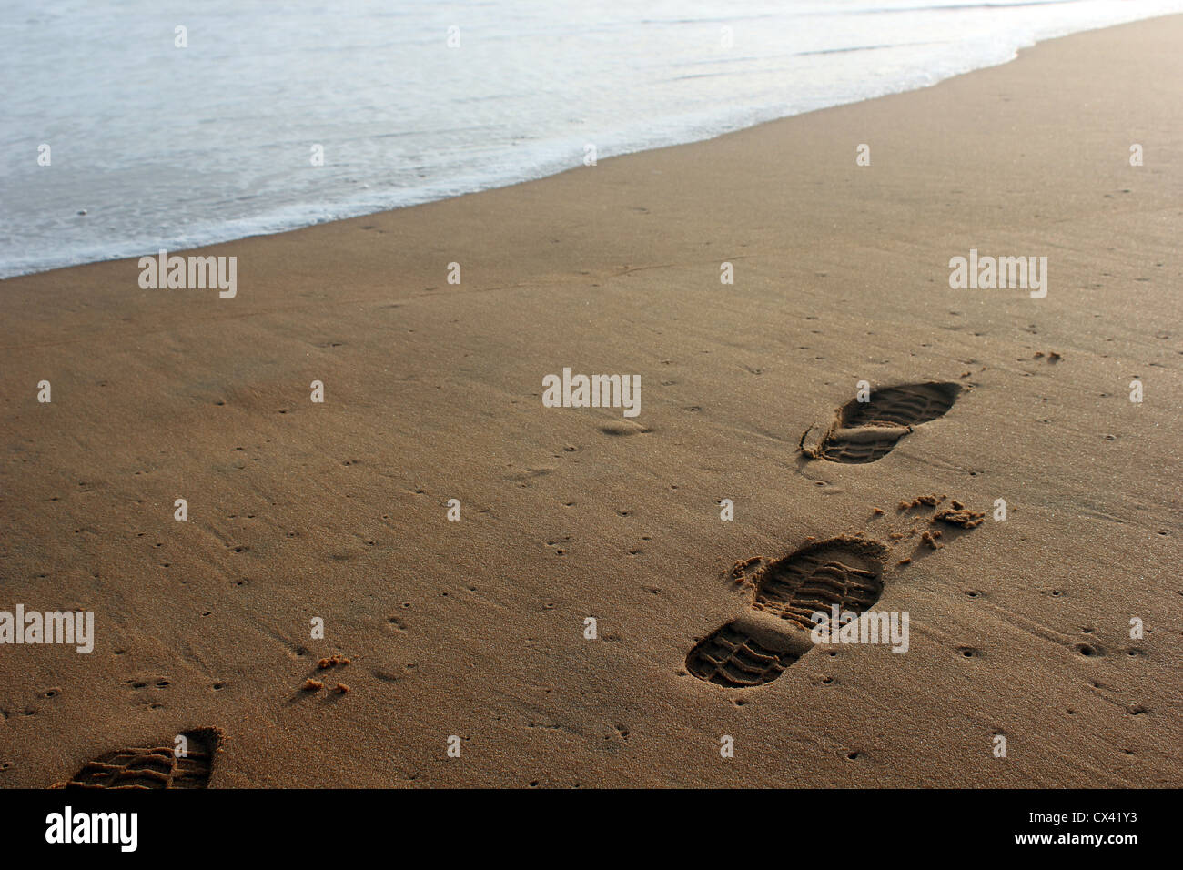 Footprint or shoe print on a beach close to the waves - Stock Image
