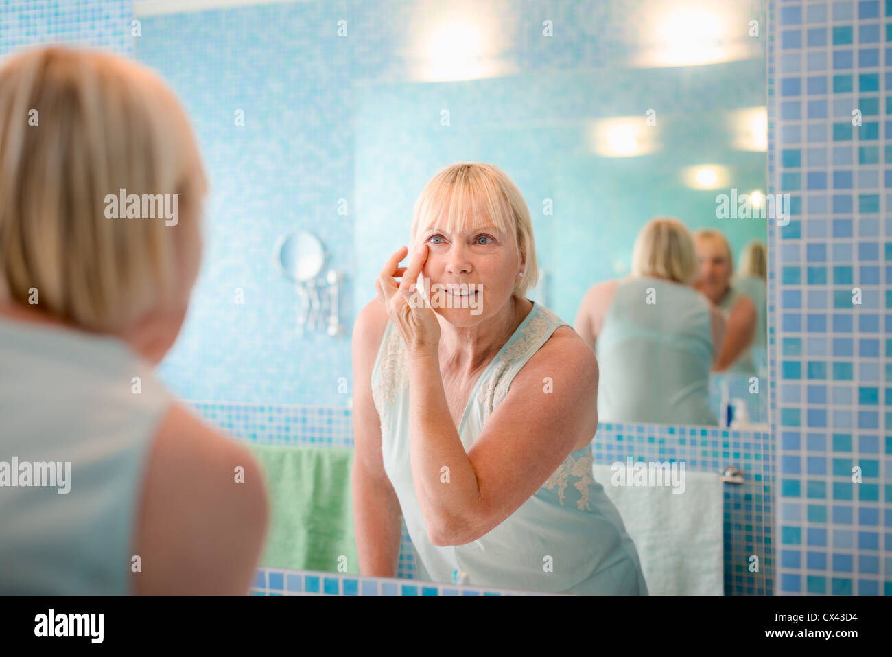 Female beauty, senior caucasian woman applying lotion on face in bathroom at home - Stock Image