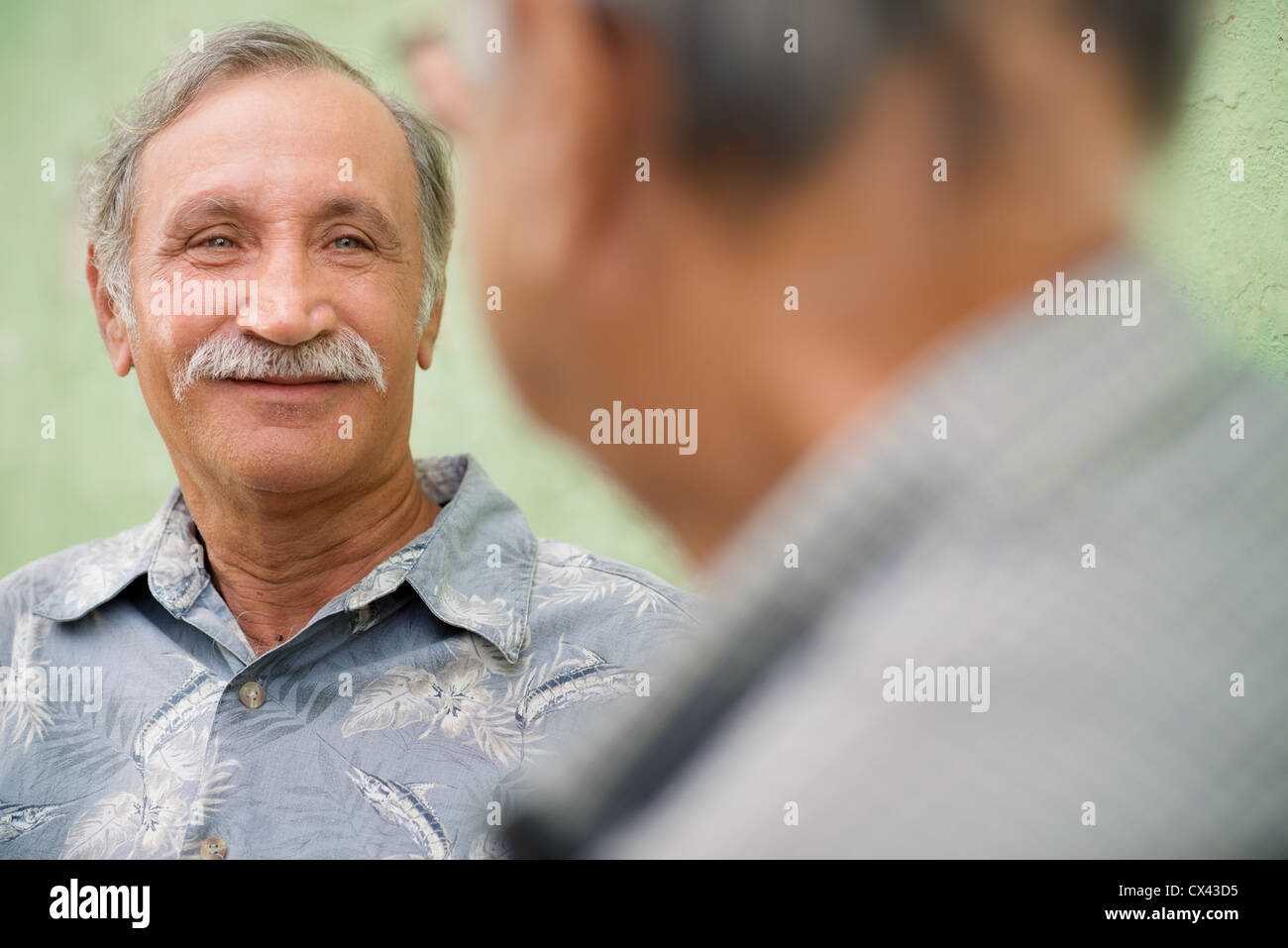 Retired elderly people and friendship, two old men meeting and talking in city park - Stock Image