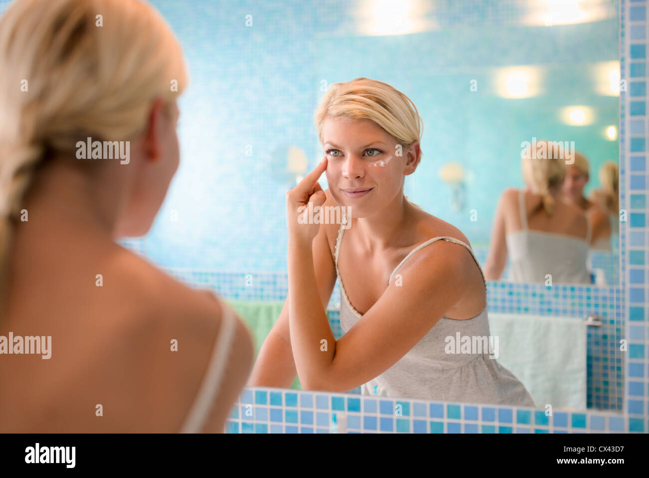 Female beauty, beautiful young caucasian woman applying cream on face in bathroom at home - Stock Image