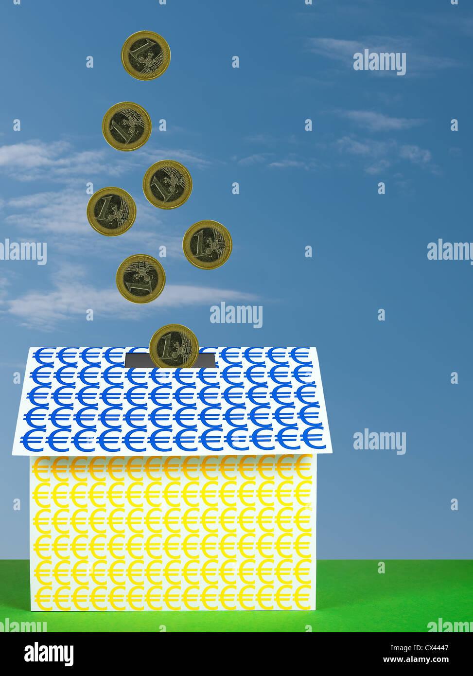Euros coins going into euro house - Stock Image