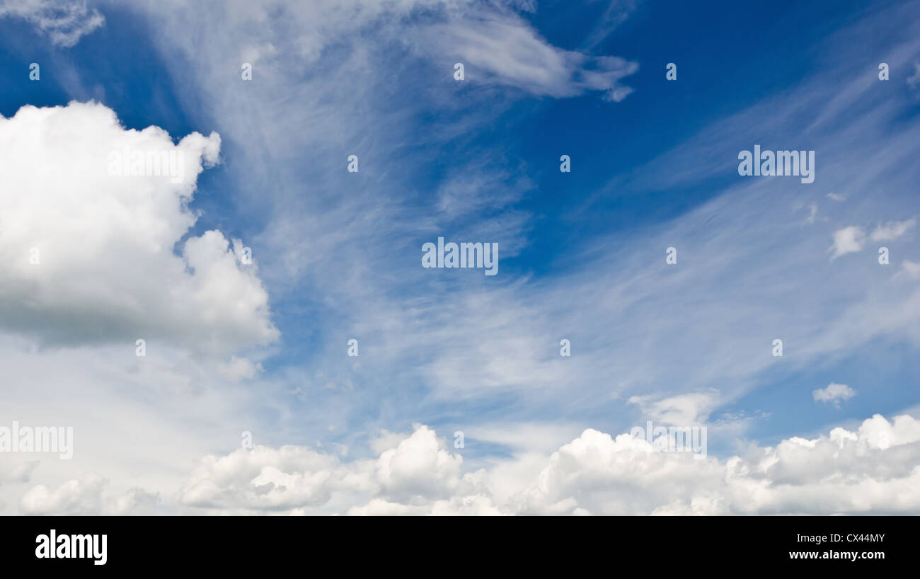 Blue Sky with wispy and thicker white clouds - Stock Image