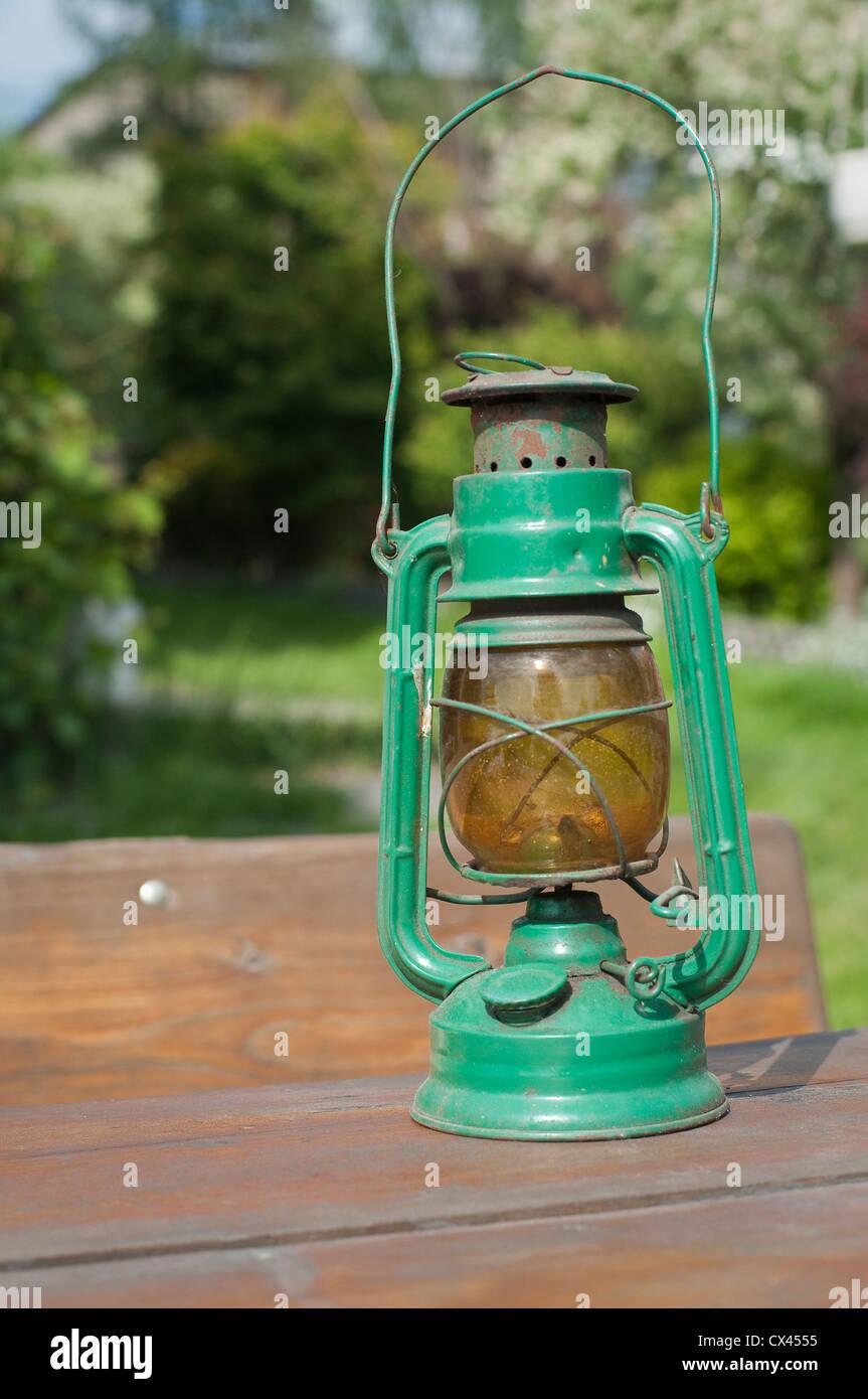Vintage kerosene lamp on table in garden - Stock Image
