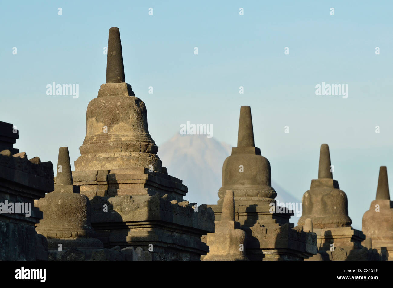 The stupa and the Merapi at the gorgeous buddhist temple of Borobudur; Central Java, Indonesia. - Stock Image