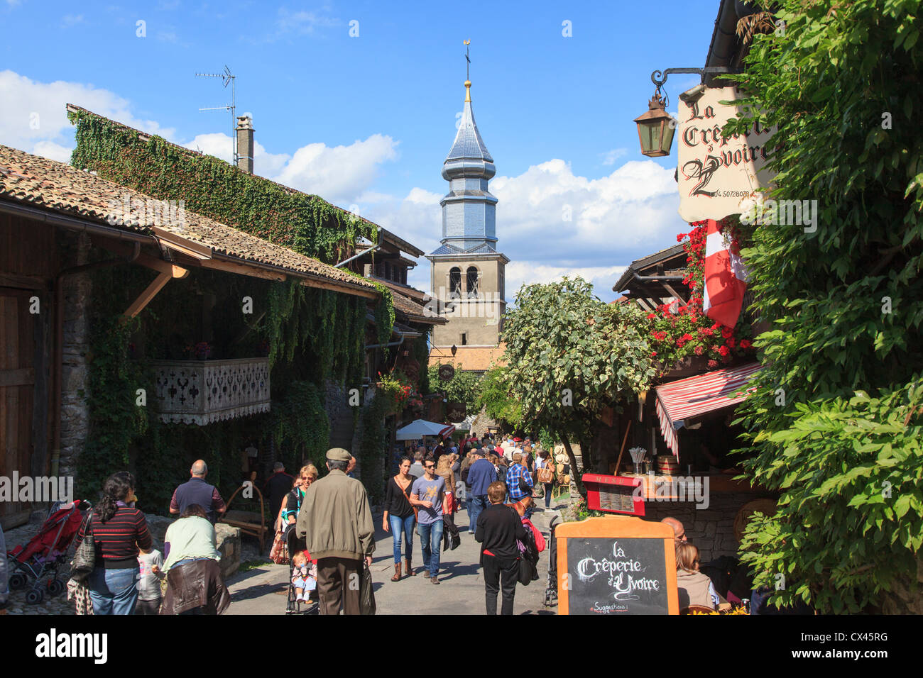 Tourist filled street in Yvoire France with the shiny steeple of the church of St Pancras in the background - Stock Image