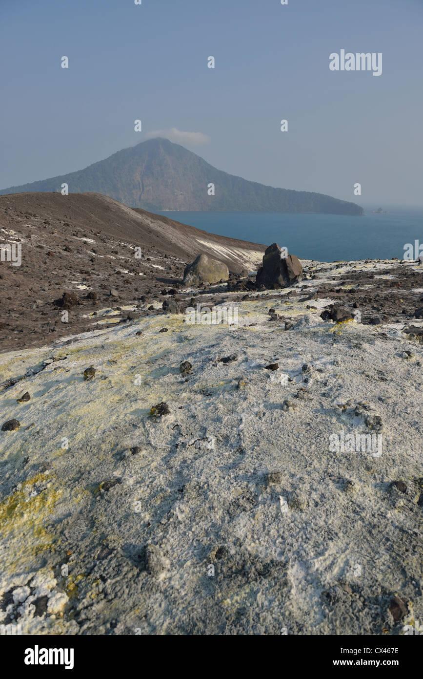 The slope covered of sulphur rich flow at Anak Krakatau with the island of Rakata in the background; Sunda Strait, - Stock Image